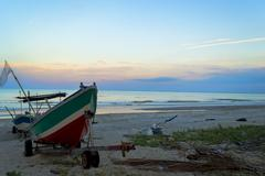 Wooden boat at beach with sunset skies Stock Photos