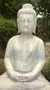 ancient buddha statue against green woods - stock photo
