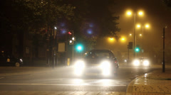 Cars Driving Down Foggy City Street at Night Stock Footage