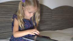 Child Playing a Game with Wireless Tablet, Ipad, Little Girl Learning ABC in Bed - stock footage
