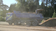 Blue truck dumping gravel at construction site Stock Footage