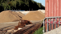A construction area with stack of iron rods and hills of soil Stock Footage
