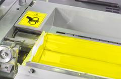 yellow ink roller, printing press industrial machine, hand caution sign for a - stock photo