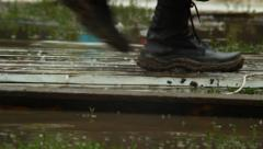 Massive military boots step on wooden platform over water, flood, click for HD - stock footage