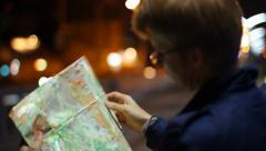 Male looking for route in tourist map foreign city night, click for HD Stock Footage
