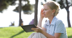 Ultra HD 4K Woman use tablet sitting park outdoors stress sad anxiety issues - stock footage