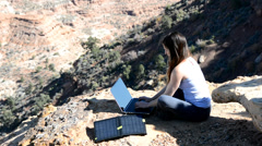 Woman Working Remotely on Laptop with Solar Panel Stock Footage
