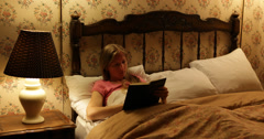 Ultra HD 4K Woman reading book lying bed night lamp illuminated bedroom home Stock Footage