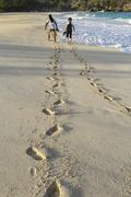 Couple stroll along beach Stock Photos
