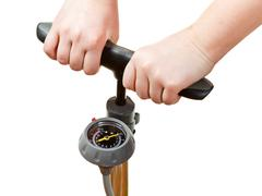 pumping by manual air pump with pressure indicator - stock photo