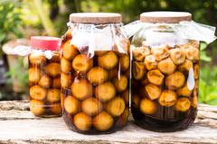pickled lemon in a glass jar - stock photo