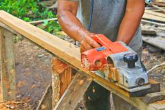 hand carpenter using wood planer - stock photo