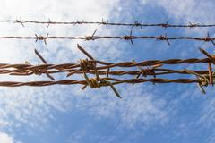 Barbed wire and blue sky Stock Photos