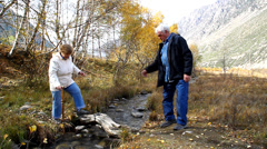 An elderly white-haired man helping his wife to move the creek on a log Stock Footage