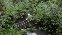 Two hikers on a bridge visit a small waterfall Stock Footage