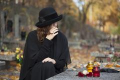 grieving woman at graveyard - stock photo