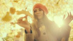 Woman playing with Autumn leaf and falling leafs with vintage color correction - stock footage