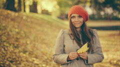 Young Woman in Autumn playing with Maple Leaf in Park vintage color correction - stock footage