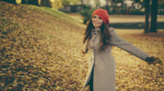 Young Woman in Autumn playing with Leaf in Park with vintage color correction - stock footage