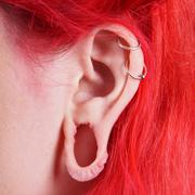 stretched ear lobe piercing - stock photo