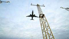 Airplane flying overhead passing airport landing lights Stock Footage