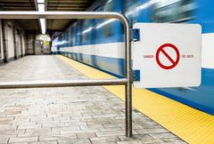 moving subway train and motion blur with safety interdiction sign. - stock photo