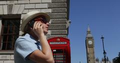 Ultra HD 4K nainen puhua matkapuhelin perinteinen punainen puhelin big ben torni Arkistovideo