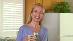 Happy mature woman drinking juice Stock Footage