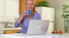 Adult woman drinking morning coffee while using computer - stock footage