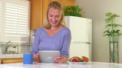 Mature woman using tablet and drinking coffee Stock Footage