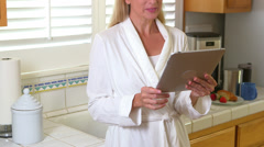 Middle Aged woman using tablet pc in kitchen Stock Footage