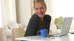 Mature woman drinking coffee and using laptop Stock Footage