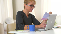 Middle aged woman drinking coffee and using laptop to pay bills Stock Footage