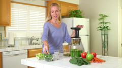 Mature woman using juicer Stock Footage