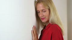 Close up of mature woman leaning against pillar - stock footage