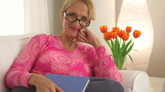 Middle aged woman smiling and holding book in living room - stock footage