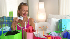 Mature woman holding credit card looking at shopping bags Stock Footage