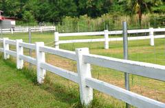 Long white fences around farm field. Stock Photos