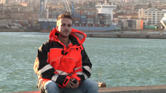 Young man make telephone call in port with orange clothes. Stock Footage