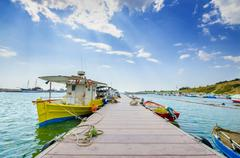 fishing marina boats on cloud blue sky and bordwalk - stock photo