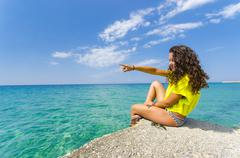 beach teen woman with curly hair pointing ocean water horizon showing vacatio - stock photo