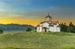 Church building on the top of the heel at sunset with orange glow from sun Stock Photos