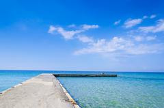 Silent place, jetty at bright vibrant sky and sea water horizon Stock Photos
