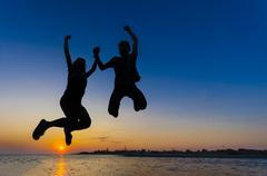 silhouette couple girl and boy jumping on the beach sunset water horizon and  - stock photo