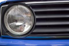 close up of old blue automobile headlight and grille - stock photo