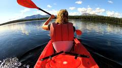 Canoeist kayaking across wilderness lake, USA Stock Footage