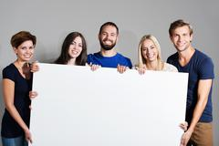 business team holding a blank sign - stock photo