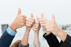 business team giving a victorious thumbs up - stock photo