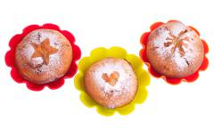 Muffin with icing sugar star, heart and sun in color forms Stock Photos