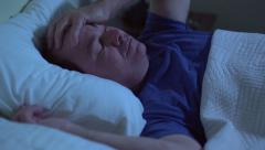 Grumpy man waking up in the middle of the night Stock Footage